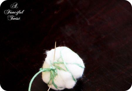 bola de algodon atada para hacer guirnalda de navidad