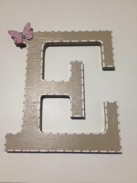 Letra de madera decorada con silueta de mariposa